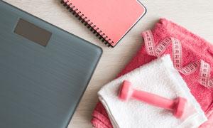 体脂秤与粉红色的哑铃摄影高清图片