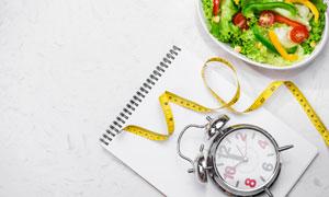 闹钟软尺与减肥用蔬菜沙拉高清图片