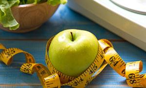 缠着软尺的青苹果特写摄影高清图片