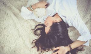 睡在毛垫上的黑发美女摄影高清图片