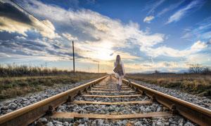 背着乐器走在铁轨上的人物高清图片