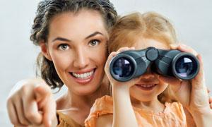家长指引下用望远镜的女孩高清图片