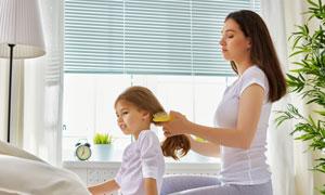让妈妈帮忙梳头发的小女孩高清图片