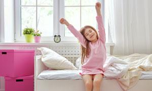 坐在床边伸懒腰的儿童摄影高清图片