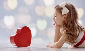 对着心形礼物的开心小女孩高清图片