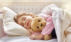 抱着玩具熊睡觉的女孩摄影高清图片