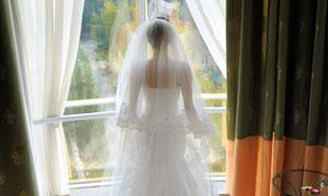 站在窗前的长拖尾婚纱新娘高清图片