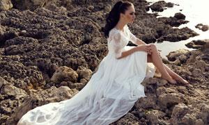 坐在礁石上的拖尾婚纱美女高清图片