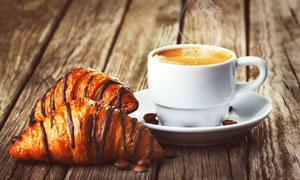 牛角面包与冒着热气的咖啡高清图片