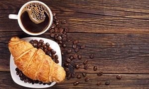 咖啡与盘子中的牛角包摄影高清图片