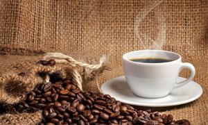 热咖啡与麻袋片上的咖啡豆高清图片