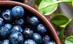 绿叶与碗里的蓝莓微距摄影高清图片