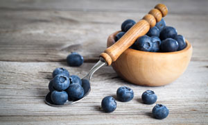 木柄勺与木碗中的蓝莓摄影高清图片