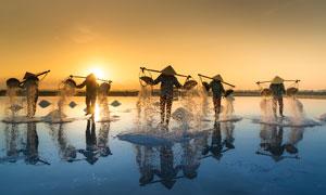 海边正在盐田劳作的人摄影图片