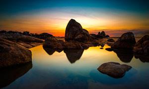 海边岩石夕阳景色摄影图片
