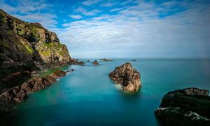 蓝天白云下的海边礁石摄影图片