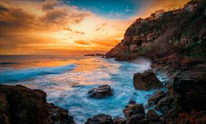 黄昏下海浪冲击着海边摄影图片