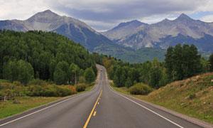 群山与公路两旁的树林摄影高清图片