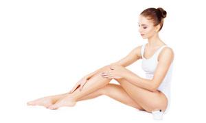 在往腿上抹乳霜的美女摄影高清图片