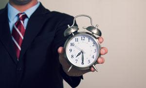手拿着闹钟的商务人物摄影高清图片