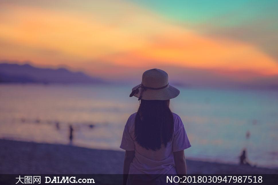 黄昏傍晚帽子长发秀发披肩发黑发背影海边海水大海海景沙滩海滩短袖