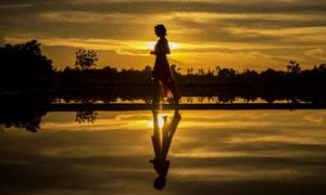 夕阳下漫步的裙装美女摄影高清图片