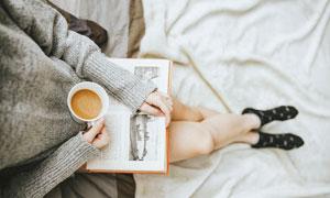 端着咖啡在看书的美女特写高清图片
