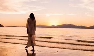 夕阳余晖下漫步的长裙美女高清图片