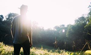 户外戴帽子的男子背影逆光高清图片