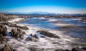 蓝天下的海边礁石景观摄影图片