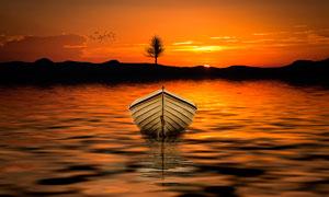 夕阳下湖中停泊的小舟摄影图片