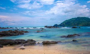 蓝天下的海边礁石和海浪摄影图片