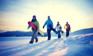 手拿着滑雪板的一行人逆光摄影图片