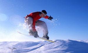 雪山风光与空中的滑雪人物高清图片