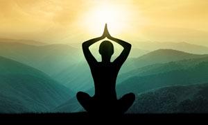 面对群山做瑜伽的人物剪影高清图片