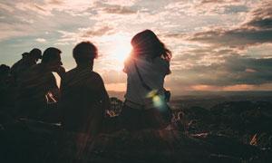 坐在山顶看日落的人群摄影高清图片