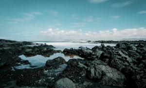 天边白云与海边的礁石风光高清图片