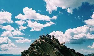 白色云朵与山顶上的登山者高清图片
