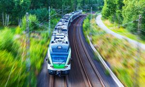 地铁列车与两侧的树丛摄影高清图片