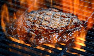 在大火烤制的美味牛排摄影高清图片