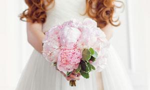 在卷发美女手中的捧花摄影高清图片