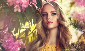 鲜花树枝掩映中的蓝眼美女高清图片