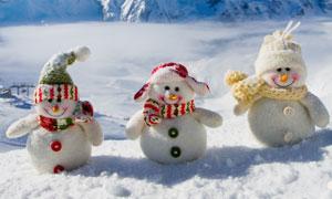 三个可爱雪人与远处的山峰高清图片