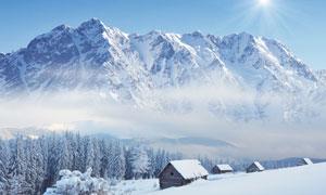 白雪覆盖的大山与房子树木高清图片