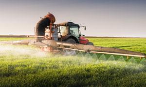 在规模化喷洒农药的拖拉机高清图片