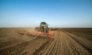 在松土犁地作业的农机摄影高清图片