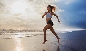 海景与甩开双臂的跑步美女高清图片