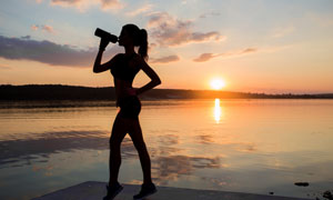 叉着腰喝水的运动美女剪影高清图片