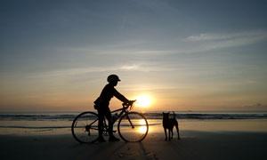 在海边沙滩上骑车人物剪影高清图片