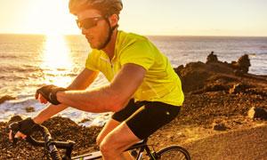 骑行路过大海边的运动人物高清图片